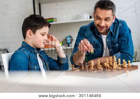 Selective Focus Of Father And Son In Denim Playing Chess While Sitting At Table At Home