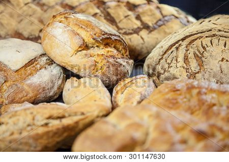 Various French breads, such as baguette, petits pains and loafs of sourdough, called pain de campagne, on display on a table. These breads are symbol of French gastronomy, made of yeast called levain poster