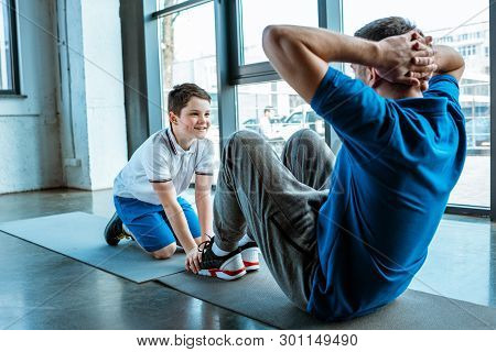 Smiling Son Helping Father Sitting On Fitness Mat And Doing Sit Up Exercise At Gym