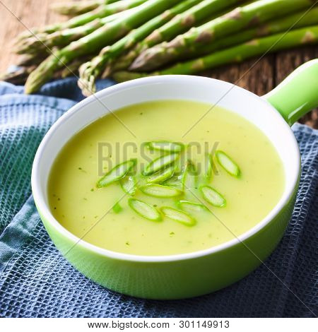 Cream Of Green Asparagus Soup In Bowl, Garnished With Sliced Asparagus On Top, Fresh Asparagus In Th