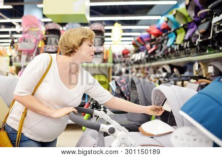 Young Beautiful Pregnant Woman Choosing Baby Stroller Or Pram Buggy For Newborn. Shopping For Expect