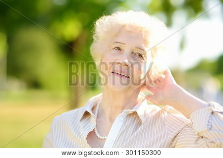 Outdoor Portrait Of Beautiful Senior Woman With Curly White Hair. Elderly Lady In Park