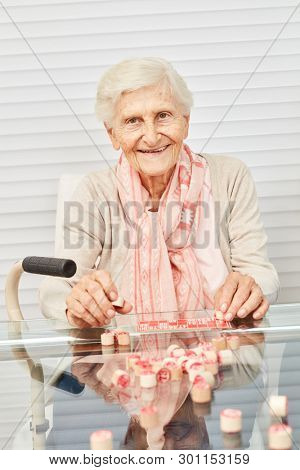 Old senior has fun playing bingo in the afternoon at the retirement home