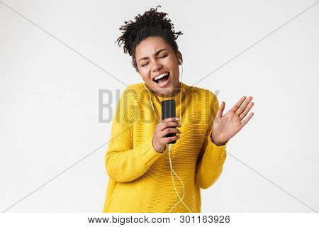 Image of a beautiful young african excited emotional happy woman posing isolated over white wall background listening music with earphones using mobile phone singing.