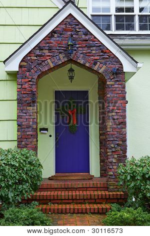 Multi-color Klinker brick borders a purple door of a yellow home