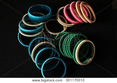 A Top View Of Plain Silk Wrapped Bangles On Black Background. These Are Handcrafted Bangles, Which A