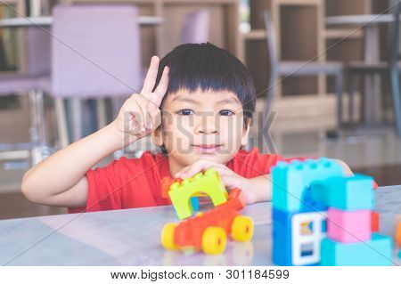 Happy Boy Surrounded By Colorful Toy Blocks Top View V Shape Hand For Victory