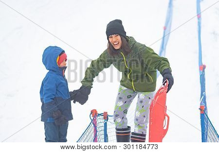 Mother Is Helping Her Boy To Ride The Sled