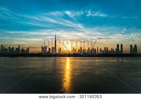 Sunrise In Dubai, Dawn, Morning Or Dusk Over Modern City. Sun Over Buildings Or Skyscrapers. Solar P