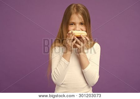 Having snacks. Child eat donut on violet background. Little girl with glazed ring doughnut on purple background. Kid with junk food. Food for snack and dessert. Childhood and childcare, copy space. poster