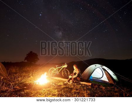 Young Woman Cyclist Resting At Night Camping Near Burning Campfire, Illuminated Tourist Tent, Mounta