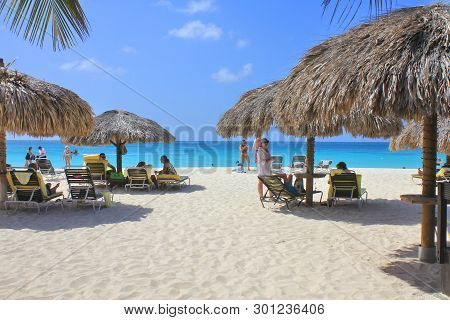 Aruba, Dutch Caribbean - February 12, 2014: Tourists On The Beautiful Caribbean Beach Of Aruba Islan