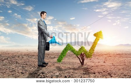 Businessman Watering Green Plant In Shape Of Of Grow Up Trend In Desert. Business Analytics And Stat