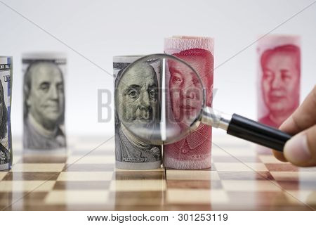 Us Dollar And Yuan Banknote With Magnifier Glass On Chess Board Which United States And China Had Ba