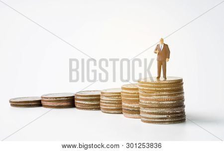 Miniature Figure Business Man Manager Standing On Glowing Coins Stack With White Background. Success