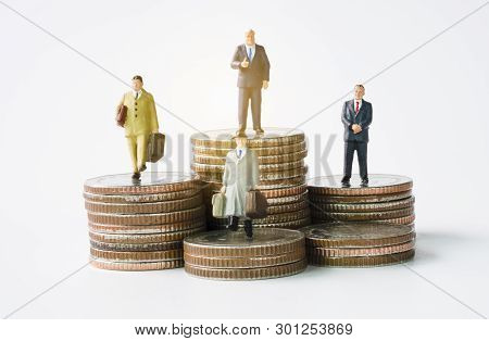 Miniature Figure Business Man Manager Standing On Glowing Coins Stack. Successful Investor Concept.