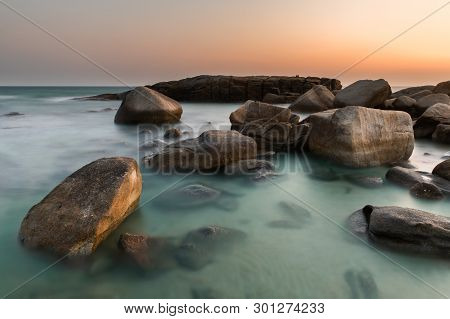 The Rock And The Sea In The Color Of Sunset Time.