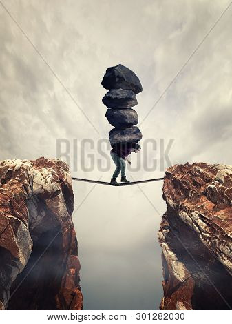 Man Carries A Stack Of Big Rocks While Balancing On A Rope Between Two Mountain Peaks.