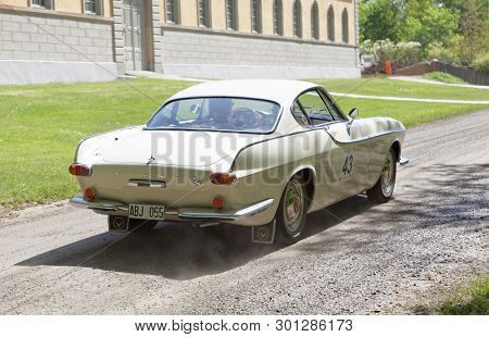 Stockholm, Sweden - May 20, 2018: White Color Volvo 1800 S Classic Car From 1963 Driving In The Publ