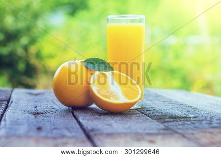 Composition With Glass Of Orange Juice Over Green Garden. Healthy Eating Concept. Glass Of Orange Ju