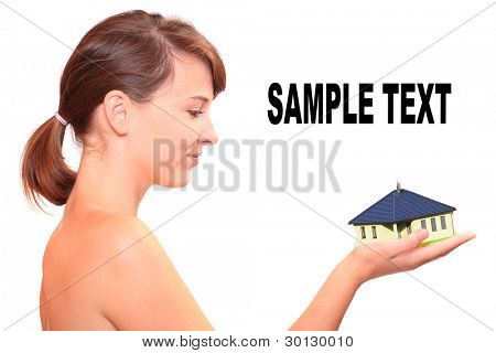 Attractive young woman holding little family house. Easy living and mortgage concept.