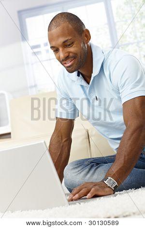 lächelnd schwarzer Mann mit Laptop-Computer zu Hause, am Boden sitzen.?