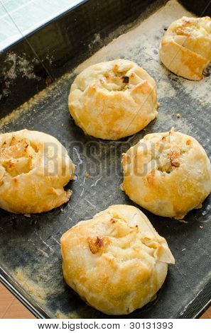 Knishes with potato and onion on baking sheet - Jewish pastry poster