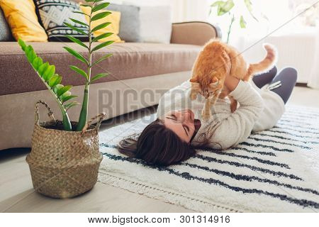 Young Woman Playing With Cat On Carpet At Home. Master Lying On Floor With Her Pet