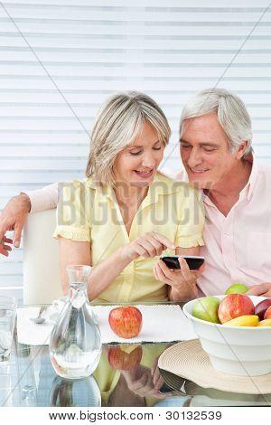Senior couple using smartphone at breakfast table