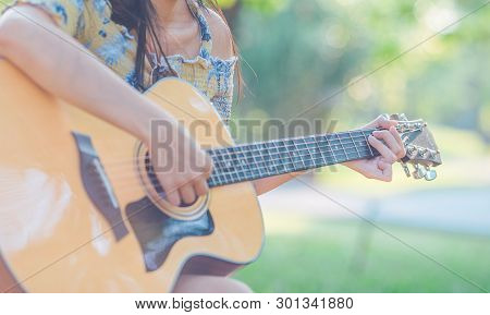Woman Is Playing Acoustic Guitar In The Garden.