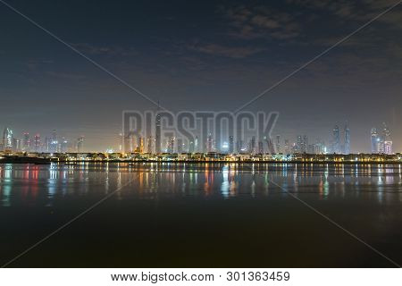 Dubai In Night City Lights. Night Or Dusk In Uae. Morning Or Sunrise, Dawn Over Dubai Downtown. View