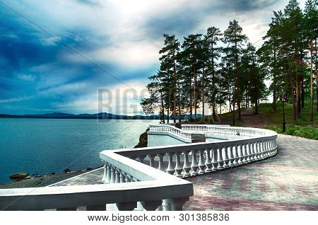 Summer sea stormy landscape - summer trees and sea under dramatic stormy sky and sculpture fence along the coast. Picturesque summer sea landscape evening scene