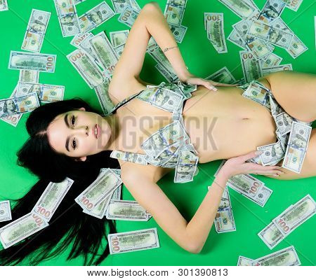 Rich Woman Lies On Money. Money Girl On Green Background. Sexy Woman In Summer Swimsuit In Currency.