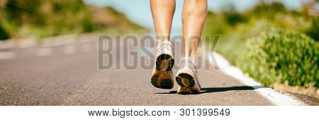 Fit run runner man jogging feet closeup running shoes banner panorama. Athletes legs walking on street for summer marathon.