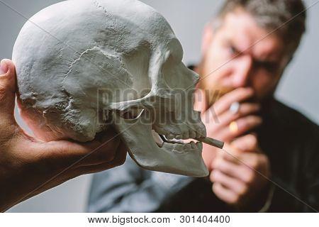 Man Smoking Cigarette Near Human Skull Symbol Of Death. Harmful Habits. Smoking Cause Health Damage