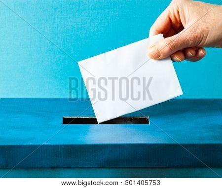 european Union parliament election concept - hand putting ballot in blue election box