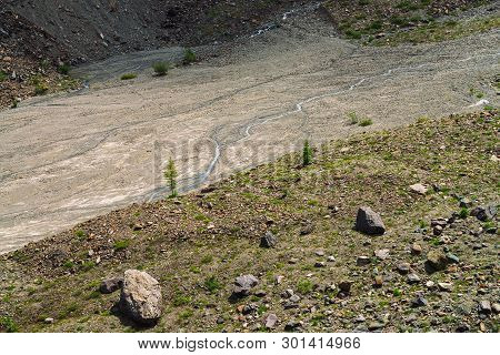 Dead Lake In Mountains With Vegetation And Stones Close Up. Brooks Flows On Ground. Streams Of Water
