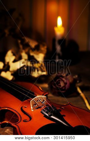 Violin, Burning Candle And Autumn Leaves On The Table