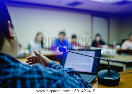 Business Man Is Presenting With Computer Laptop And Microphone In Conference Room