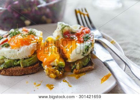 Breakfast Served Of Two Toasts With Avocado, Fried Eggs With Vegetables And Herbs On A Rustic Tablec