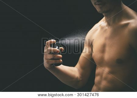 Young Man Spraying Perfume On Black Background