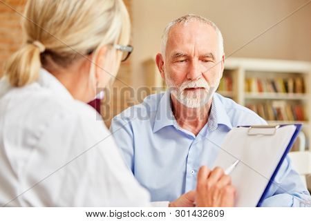 Female doctor with clipboard interviews senior man as a patient in the anamnesis