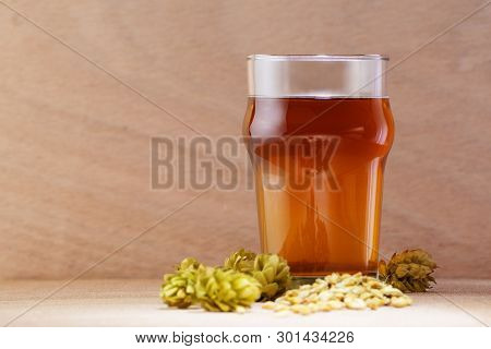 Beer In A Glass With Barley And Hops On Wooden Background. Craft Beer, Brewery And Alcohol Beverage