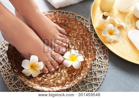 Closeup View Of Woman Soaking Her Feet In Dish With Water And Flowers On Grey Floor. Spa Treatment