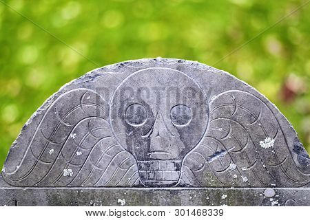 A skull on an old headstone at the Old Granary Burial ground on the freedom trail in boston massachusetts. poster