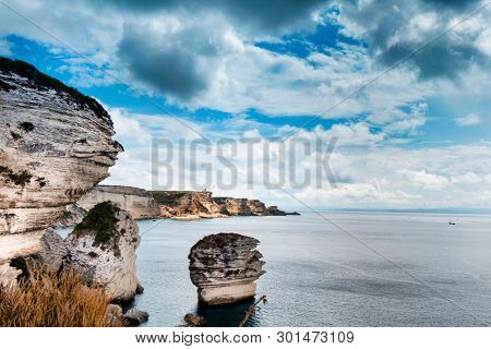 a view of the picturesque landscape of cliffs over the Mediterranean sea in Bonifacio, Corsica, in France, highlighting the famous Grain de Sable sea stack in the center