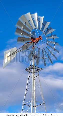 Clear Vertical Shiny Steel Windpump Against A Vibrant Blue Sky With Cottony Clouds