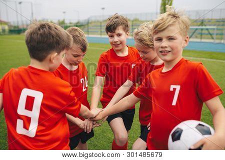 Kids On Football Soccer Team Putting Hands In. Boys Football School Team Huddling. Children Hands To