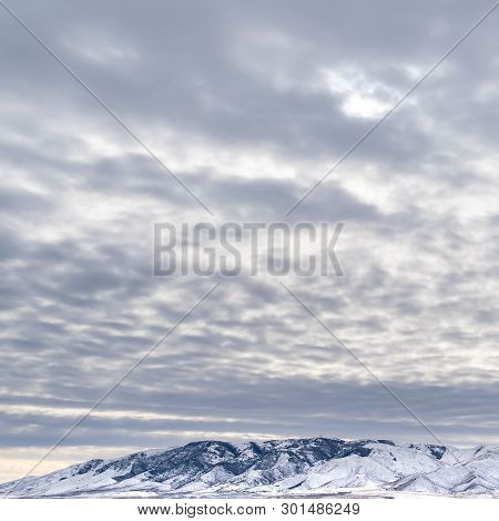 Square Dramatic Sky Filled With Cottony Clouds Over A Scenic Landscape In Winter