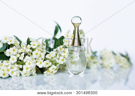 Perfume And Small White Flowers On White